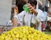 کوئٹہ: سبزی منڈی میں ایک ریڑھی بان لیموں پر پانی چھڑک رہا ہے۔