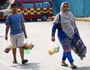 لاہور: خاتون بچے کے ہمراہ سستا رمضان بازار سے افطاری کے لیے فروٹ خرید ..