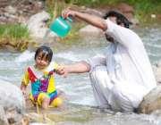اسلام آباد: ایک شخص اپنی بچی کو گرمی کی شدت سے بچانے کے لیے نہلا رہا ..