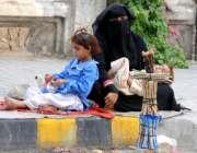 راولپنڈی:ایک خاتون اپنے دو کمسن بچوں کے ہمراہ سڑک کنارے مسواک رکھے ..