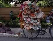اسلام آباد:ہاتھ سے بنائی چیزیں فروخت کرنے والا ایک محنت کش دوپہر کے ..