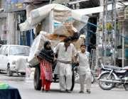 راولپنڈی: ایک محنت کش اپنے بچوں کے ہمراہ وزن سے لدھا ریڑھا کھینچتے ہوئے ..