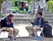 لاہور: دو پولیس اہلکا دوران ڈیوٹی نہر کنارے بیٹھے آرام کر رہے ہیں۔