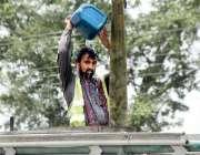 لاہور: گرمی کی شدت کم کرنے کے لیے ایک محنت کش نہا رہا ہے۔