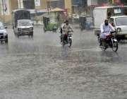 لاہور: صوبائی دارالحکومت میں موسلا دھار بارش کے دوران موٹر سائیکل سوار ..