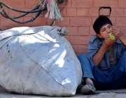 راولپنڈی: خانہ بدوش بچہ فٹ پاتھ پر بیٹھا انگور کھا رہا ہے۔