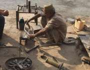 لاہور: ایک محنت کش سڑک کنارے ویلڈنگ کی دکان لگائے کام میں مصروف ہے۔