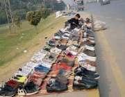 فیصل آباد: فٹ پاتھ پر پرانے جوتوں کا سٹال لگائے کمسن بچہ جوتوں کو مرمت ..