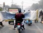 لاہور: موٹر سائیکل سوار بڑے سائز کے گاڑی کے پارٹس لیکر جا رہے ہیں جس ..