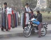 لاہور: ایک موٹر سائیکل سوار سردی کی شدت سے بچنے کے لیے مفلرخرید رہا ..