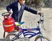 راولپنڈی: ایک بچہ اپنے سائیکل پر سلنڈر رکھے گیس بھروانے کے لیے جا رہا ..