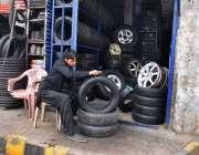 لاہور: ایک دکاندار گاڑی کے پرانے ٹائر صاف کرنے میں مصروف ہے۔