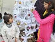 لاہور: ایک بچی کرسمس کی تیاریوں کے سلسلے میں کرسمس ٹری سجا رہی ہے۔