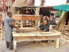 LAHORE: A carpenter busy in giving the final touch to the wooden cart for animal fodder at their workplace in the Provincial Capital.