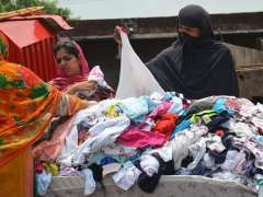 LAHORE: Womens buying second hand cloths from a roadside vendor on ring road.