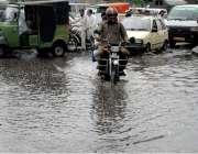 راولپنڈی: موسلا دھار بارش کے بعد ایک موٹر سائیکل سوار بارش کے پانی سے ..