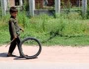 راولپنڈی: ایک خانہ بدوش بچہ پرانے ٹائر سے کھیل رہا ہے۔