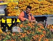 راولپنڈی: دکاندار گاہکوں کو متوجہ کرنے کے لیے کینو سجائے بیٹھا ہے۔