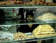 راولپنڈی: عید کی آمد کے موقع پر ایک دکاندار اپنی دکان میں بیکری آئٹم ..