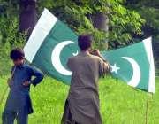 اسلام آباد: دو نوجوان سڑک کنارے قومی پرچم فروخت کے لیے سجائے بیٹھے ہیں۔