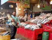 فیصل آباد: مچھلی فروش مچھلی کا سٹال لگائے گاہکوں کا منتظر ہے۔
