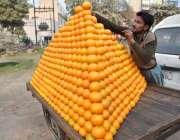 لاہور: ایک ریڑھی بان خوبصورت انداز میں کینو فروخت کے لیے سجا رہا ہے۔