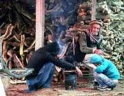 راولپنڈی: خانہ بدوش خاندان کے افراد سردی کی شدت سے بچنے کے لیے آگ جلائے ..