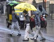راولپنڈی: سکول سے چھٹی کے بعد بچے بارش سے بچنے کے لیے چھتری تانے جا رہے ..