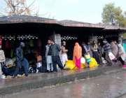 اسلام آباد: شہریوں کی بڑی تعداد بارش سے بچنے کے لیے ایک شیلٹر کے نیچے ..