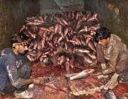 لاہور: مچھلی فروش مچھلی کی صفائی میں مصروف ہیں۔