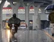 راولپنڈی: ایک موٹر سائیکل سوار دوران بارش برساتی پہنے اپنے منزل کی ..