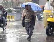 راولپنڈی: ایک معمر شخص بارش کے دوران چھتری تانے جا رہا ہے۔