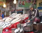 فیصل آباد: مچھلی فروش مچھلی بنانے میں مصروف ہے۔
