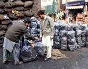 لاہور: ایک شہری ٹال سے کوئلے خرید رہا ہے۔