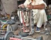 لاہور: ایک بزرگ کاریگر گھاس کاٹنے والی مشین مرمت کرنے میں مصروف ہے۔