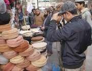 لاہور: شہری سردی کی شدت سے بچنے کے لیے ایک سٹال سے گرم ٹوپیاں خرید رہے ..