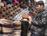 لاہور: ایک شہری سردی کی شدت سے بچنے کے لیے ایک سٹال سے گرم ٹوپی پسند ..
