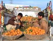 اسلام آباد: دو محنت کش سڑک کنارے سوزوکی پک اپ میں رکھے اورنج فروخت کر ..