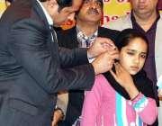 فیصل آباد: ڈی سی او سلمان غنی ایک بچی کے کان پر قوت سماعت کا آلہ لگا رہے ..