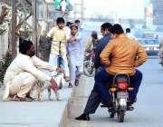 ملتان: ایک شخص بکری کے دو بچے فروخت کرنے کے لیے فٹ پاتھ پر بیٹھا ہے۔