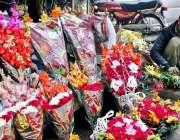 لاہور: ایک دکاندار فروخت کے لیے پھولوں کے گلدستے بنانے میں مصروف ہے۔