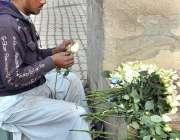 اسلام آباد: ایک محنت کش سڑک کنارے فروخت کے لیے پھولوں کا سٹال لگائے ..