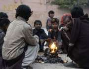 راولپنڈی: خانہ بدوش خاندان کے افراد سردی کی شدت کم کرنے کے لیے آگ جلائے ..