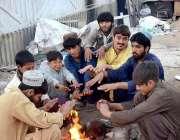 کراچی: مزدور سردی کی شدت کو کم کرنے کے لیے آگ جلائے بیٹھے ہیں۔
