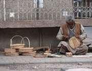 راولپنڈی: ایک مزدور فٹ پاتھ پر بیٹھا روایتی ٹوکریاں بنا رہا ہے۔