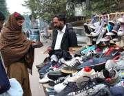 سیالکوٹ: ایک شہری ریڑھی بان سے جوتا پسند کر رہا ہے۔