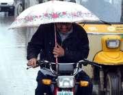 سرگودھا: ایک موٹرسائیکل سوار بارش سے بچنے کے لیے چھتری تانے جا رہا ہے۔