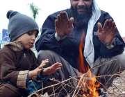 سرگودھا: ایک شخص اپنے بچے کے ہمراہ سردی کی شدت کم کرنے کے لیے آگ جلائے ..
