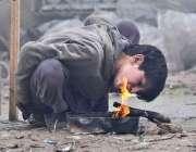 اسلام آباد: ایک خانہ بدوش بچہ سردی کی شدت سے بچنے کے لیے آگ جلا رہا ہے۔