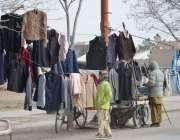 کوئٹہ: ہدہ جیل کے قریب اسٹال پر ایک شخص گرم ملبوسات فروخت کرنے کے لیے ..